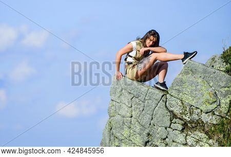 On Edge Of World. Woman Sit On Edge Of Cliff In High Mountains Blue Sky Background. Hiking Peaceful