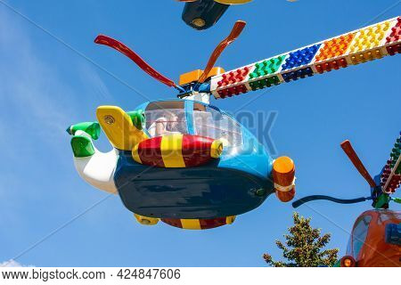 Children's Carousels Helicopters In An Amusement Park, Carousels And People During The Summer In The