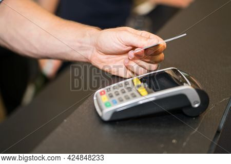 Focus On Hand Making Credit Card Payment Closeup With Male Hand Holding Card Above Reader.