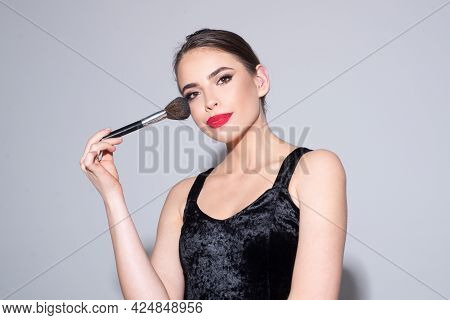 Beautiful Woman Putting Blush With Cosmetic Brush. Close Up Face Beauty Portrait.