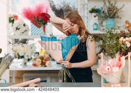 Florist Woman Making Bouquet In Flower Boutique.