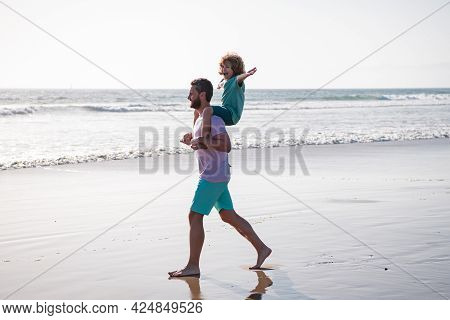 Father And Son Walking On Sea. Handsome Man Father Carrying Young Boy Son. Happy Dad Holding Child.