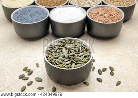 Pumpkin Seeds. Peeled Pumpkin Seeds Are In A Black Saucer. On A Black Cutting Board Made Of Stone
