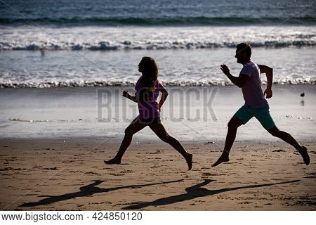 Young Man And Woman Running Jogging Along The Sea. Couple Running On Beach.