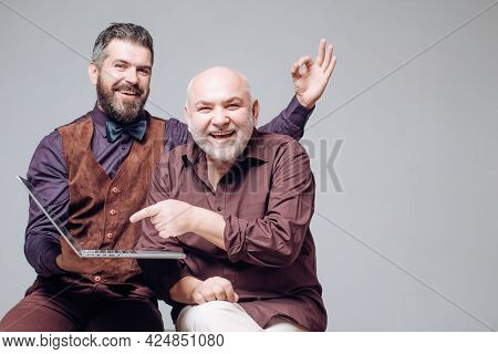 Happy Young Man With Senior Dad Have Fun Watching Funny Video On Laptop, Smiling Elderly Father And