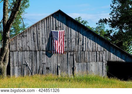American Flag Hanging On Old Weathered Farm Barn