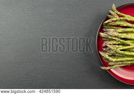 Green Asparagus On A Black Slate Stone Background. Top View, Asparagus In A Red Plate. Culinary Bann