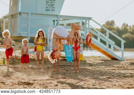 Six Cute Blond Kids In Summer Clothes Looking At The Jumping Teen Boy At The Sand Beach With Blue Li