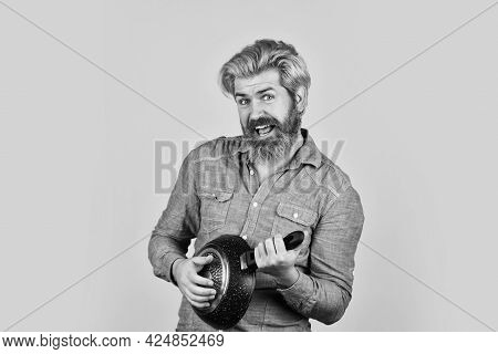 Cook Playing On Guital Pan. Bearded Man Hold Cooking Pan. Cook Preparing Food In Kitchen. Husband On