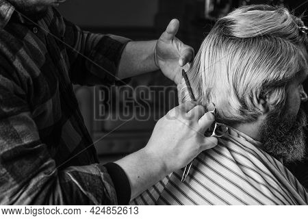 Cut Hair. Barber Making Hairstyle For Bearded Man Barbershop Background. Guy With Long Dyed Blond Ha