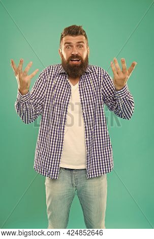 Confused Bearded Man In Casual Checkered Shirt On Blue Background, Embarrassment