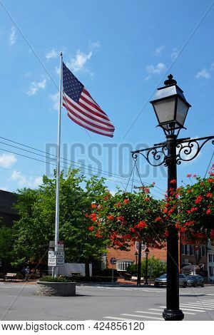 COOPERSTOWN, NEW YORK - 21 JUNE 2021: Flag and lamppost at the intersection of Main Street and Pioneer Street in the upstate town and home of the National Baseball Hall of Fame.