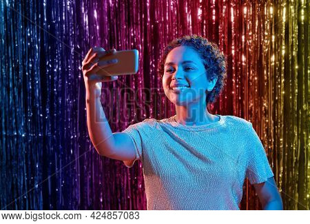 nightlife, technology and people concept - happy young african american woman taking selfie with smartphone at party in neon lights over rainbow foil curtain background