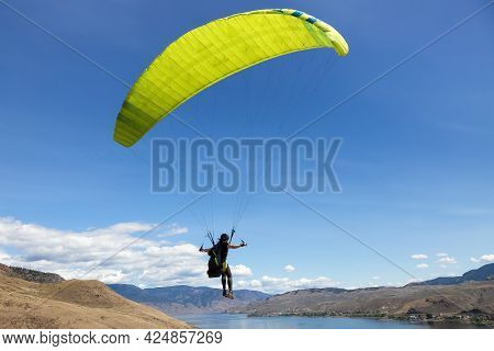 Adventurous Caucasian Adult Woman Learning To Fly On A Paraglider Around The Mountains. Savona, Brit
