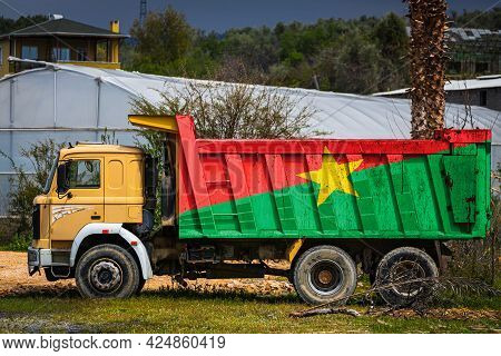 Dump Truck With The Image Of The National Flag Of Burkino Faso Is Parked Against The Background Of T