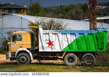 Dump Truck With The Image Of The National Flag Of Djibouti Is Parked Against The Background Of The C