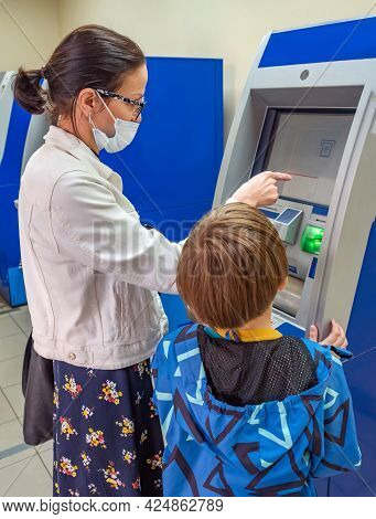 Middle-aged Woman In A Protective Mask With A Boy Use An Atm Machine.