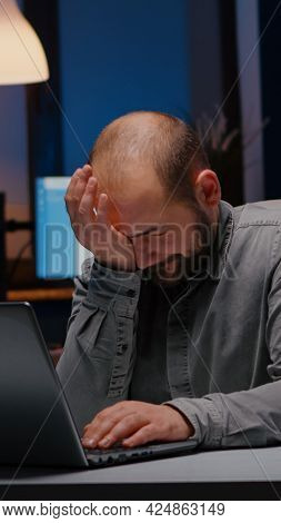 Overworked Businessman Rubbing Face While Working At Financial Statistics Using Laptop Late At Night