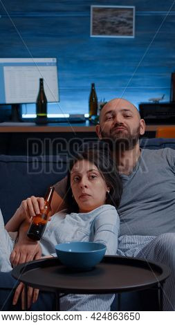 Relax Couple In Pajamas Sitting On Sofa Eating Popcorn Watching Tv, Enjoying Free Time Together Look