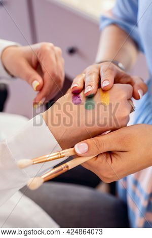 Closeup Hands Of Professional Female Visagist Applying Colorful Swatches Of Trendy Eyeshadow