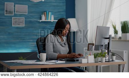 African American Student Sitting At Desk Table Start Typing Online Homework Using Computer Browsing