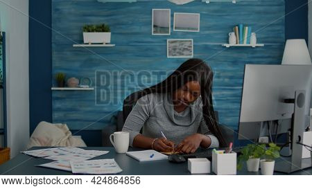 Black Student Writing School Ideas On Stickey Notes Working At Homework Sitting At Desk Table In Liv