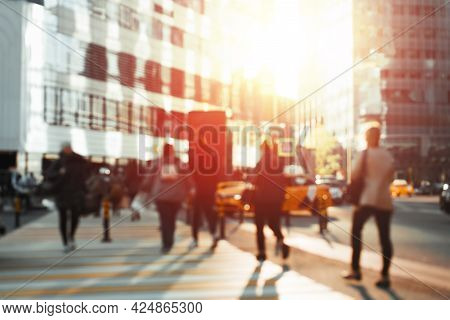 Group Of People In Bokeh Crossing The Road In The Business Center Of The City. Silhouettes Of People