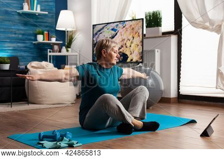 Retired Senior Woman Searching Fitness Tutorial On Laptop Sitting On Yoga Mat Streching Arm During W