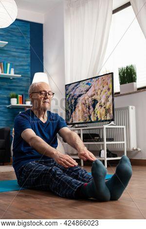 Retirement Senior Man Sitting On Yoga Mat Stretching Legs Muscles During Body Training Working At Fl