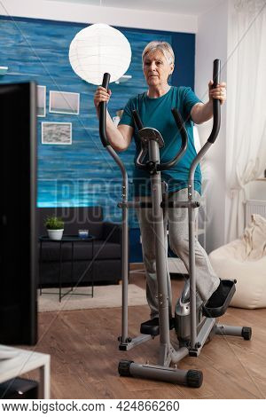 Focused Senior Woman Working Muscle Legs Doing Body Exercise Using Cycling Bicycle Machine During Fi