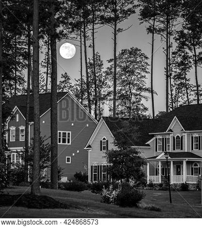 Black and white image of full moon rising over residential houses