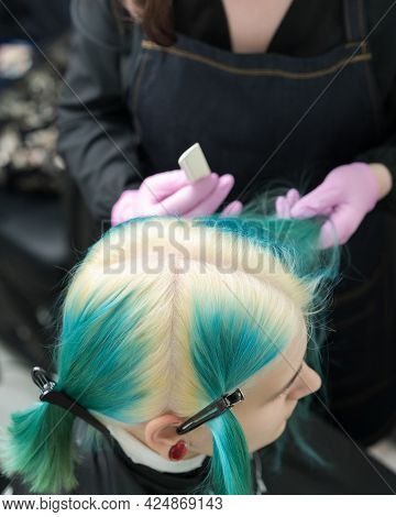 Top View Of Head Of Young Woman With Green Hair And Bleached Hair Roots, Hair Parting. Female In Pro