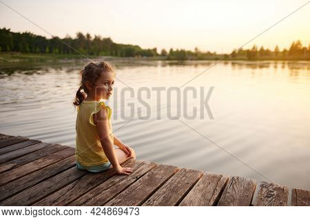 Cute Baby Girl Relaxing On The Pier At Sunset. Warm Summer Evening. Heat Summer, Summer Evenings In