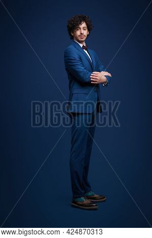 Men's fashion. Full length portrait of a handsome brunet man in elegant classic suit and a bow-tie posing at studio on a dark blue background.