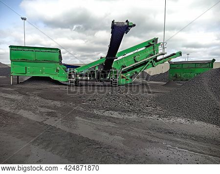 Mechanized Loading Of Bulk Cargo. Heaps Of Gravel On The Dock And A Harvester With Transport Belts.