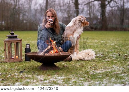 Australian Shepherd Sits Next To His Owner By The Fire. The Woman Drinks Coffee From A Thermos Cup.