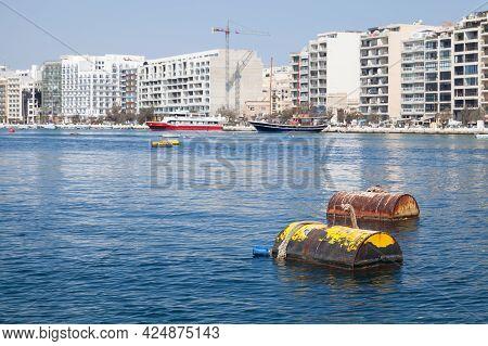 Rusty Yellow Mooring Buoys Float In Port Of Sliema, Malta