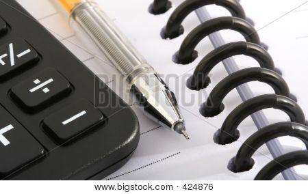 Ballpen And Calculator On Notebook
