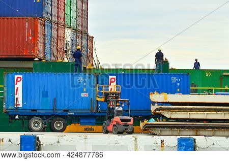 Labuan,malaysia-may 20,2021:big Containers Being Unloaded From A Huge Cargo Ship In The Labuan Conta