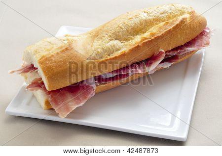 closeup of a spanish serrano ham sandwich served in a plate