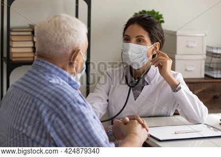 Female Doctor In Facemask Listen To Old Patient Heart