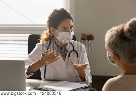 Caucasian Female Doctor Consult Old Patient In Facemask
