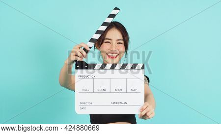 Asian Woman Holding White Clapperboard Or Movie Clapper Board On Green Mint Or Tiffany Blue  Backgro