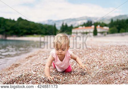 Little Girl Kneels On A Pebble Beach Near The Water
