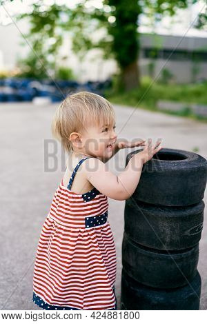 Smiling Little Girl Stands Near A Pile Of Small Tires In A Parking Lot