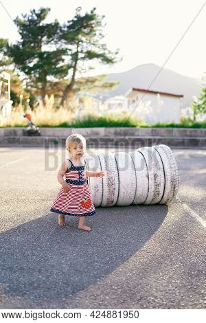 Little Girl Stands Near White Tires In The Parking Lot