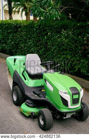 Green Large Lawn Mower Stands On The Asphalt In The Park