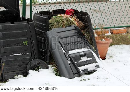 Broken Old Destroyed Almost Full Black Plastic Compost Bin Next To Flower Pot And Metal Fence In Bac