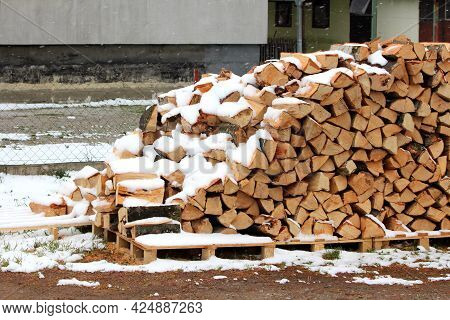 Freshly Cut Firewood Neatly Stacked On Top Of Wooden Pallets Covered With Falling Snow In Front Of S