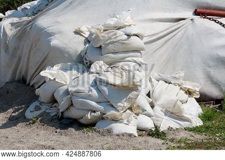 Pile Of New White Sandbags Used For Flood Protection Next To Temporary Flood Protection Wall Made Of